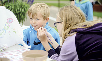 Blayne Becker, 4, waits patiently as Trinity Osberg paints his face.