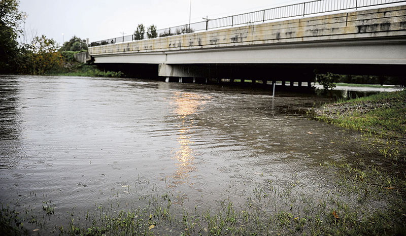 Rain falls on an already swollen Turtle Creek under Oakland Avenue West Thursday morning. Eric Johnson/photodesk@austindailyherald.com