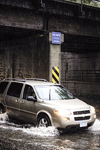An SUV drives through high water underneath the 2004 High Water mark sign on Oakland Place Southeast.
