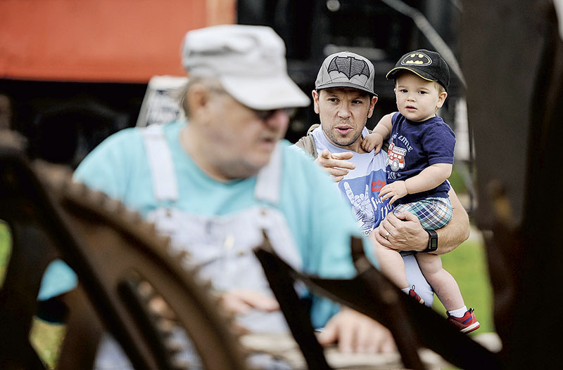 Paul White and his 22-month-old son, Franklin, watch as an old bailer is brought up to speed.