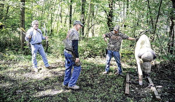 Jake VandeZande, from right, Walk Wollenburg and Larry Erikson retrieve arrows from a target at the Cedar River Archery Club. Eric Johnson/photodesk@austindailyherald.com