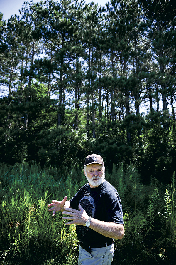 Jay C. Hormel Nature Center naturalist Larry Dolphin talks about his time at the center as he walks past some of the pine trees that populate the land. Eric Johnson/photodesk@austindailyherald.com