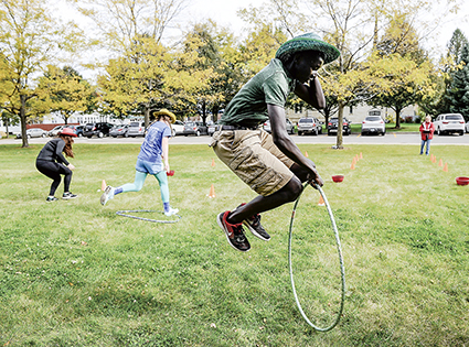 Sophomore Okuny Awow jumps through a hulu hoop during an obstacle course for Battle of Connects Friday.