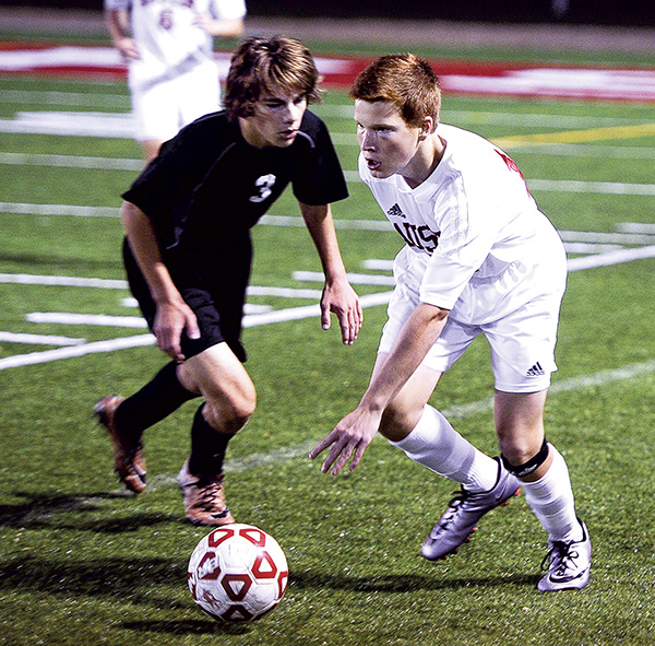 Austin's Caleb Simerson takes the ball past Caledonia's Braden Olinger during their first-round matchup in the Section 1A Tournament Tuesday night at Art Hass Stadium. Eric Johnson/photodesk@austindailyherald.com