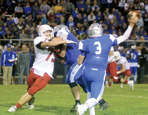 Austiin's Luke Hawkshead pressures Owatonna quarterback Abe Havelka in Owatonna Friday. Rocky Hulne/sports@austindailyherald.com