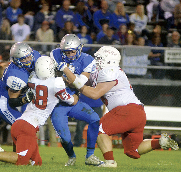 Corey Waller, left, Elijah Marks, right, team up on a tackle against Owatonna's Jason Williamson in Owatonna Friday. Rocky Hulne/sports@austindailyherald.com