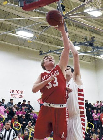 Kyle Oberbroeckling goes up for an inside shot against Mankato West's Michael Sathoff in Packer Gym Monday. Rocky Hulne/sports@austindailyherald.com
