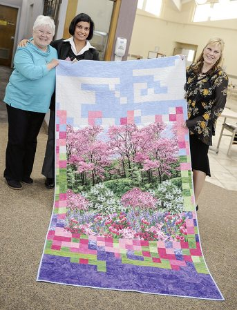 Carol Hancuh, from left, Anu Thawani and Sacred Heart director Kim Klingfus hold up one of two quilts Hancuh doanted to Sacred Heart. Eric Johnson/photodesk@austindailyherald.com
